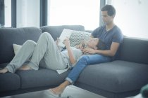 Couple with tablet relaxing at home — Stock Photo
