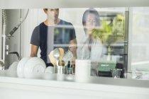 Pareja de pie en la cocina moderna - foto de stock