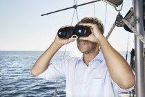 Человек с биноклем на лодке — стоковое фото