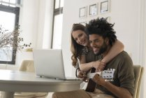 Smiling couple sitting in front of laptop — Stock Photo