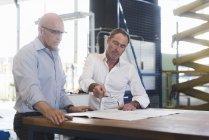 Unternehmer diskutieren Plan auf Tisch — Stockfoto