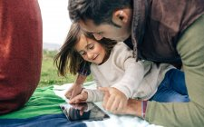 Happy girl with father using tablet — Stock Photo