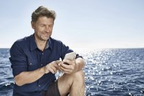 Mature man on sea using cell phone — Stock Photo