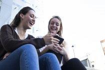 Друзья сидят на лестнице и используют мобильный телефон — стоковое фото