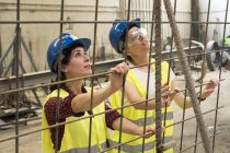 Female workers setting up iron reinforcement — Stock Photo