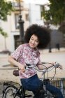 Жінка, сидячи на велосипеді, спостерігаючи те — стокове фото