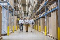 Men walking in factory warehouse — Stock Photo