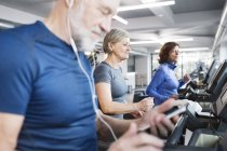Seniors working out on treadmills in gym — Stock Photo