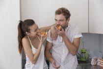 Pareja comiendo pizza en la cocina - foto de stock