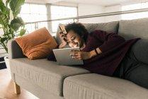 Frau auf Couch mit Kreditkarte und tablet — Stockfoto