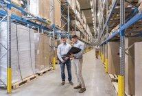 Мужчины разговаривают на фабричном складе — стоковое фото