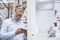 Man examining product in factory — Stock Photo