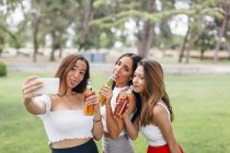 Friends drinking beer and taking selfie — Stock Photo