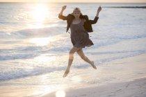 Donna, saltando sulla spiaggia — Foto stock