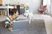 Femme sur plancher regarder chien — Photo de stock