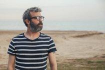 Hombre con barba en la playa - foto de stock