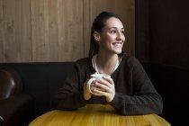 Mulher com xícara de café no café — Fotografia de Stock