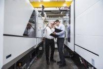Zwei Männer reden unter Maschinen — Stockfoto