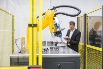 Controllo robot industriale uomo d'affari — Foto stock