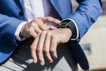 Uomo d'affari con smartwatch al polso — Foto stock