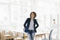 Businesswoman sitting on desk in office — Stock Photo