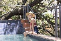 Woman sitting at swimming pool — Stock Photo