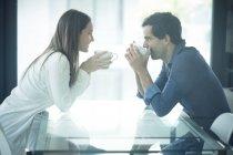 Пара сидит за столом с кофейными чашками — стоковое фото
