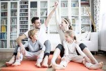 Happy family doing gymnastics — Stock Photo