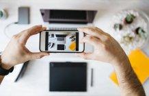 Man taking a photo of his desktop — Stock Photo