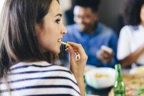 Mujer comiendo papas fritas - foto de stock