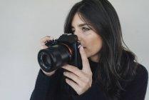 Giovane donna con una macchina fotografica — Foto stock