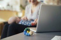 Juguete de bebé al lado del ordenador portátil - foto de stock