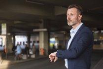 Uomo d'affari in attesa al terminal degli autobus — Foto stock