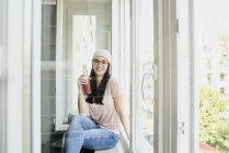 Frau mit Flasche auf Fensterbank — Stockfoto