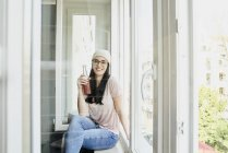 Woman holding bottle on window sill — Stock Photo