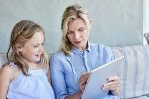 Madre e figlioletta utilizzando tablet — Foto stock