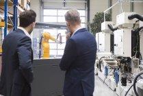 Geschäftsleute, die Prüfung der Industrieroboter — Stockfoto