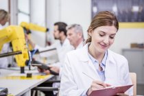 Engineer in factory taking notes on clipboard — Stock Photo