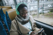 Jovem mulher em uma musica de ônibus — Fotografia de Stock