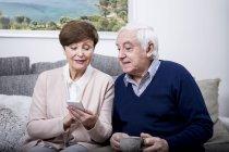 Senior couple using smartphone — Stock Photo