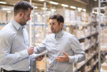 Men discussing in factory warehouse — Stock Photo