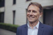 Empresário ao ar livre com fones de ouvido — Fotografia de Stock
