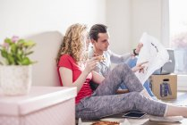 Young couple in new home sitting on floor and discussing ground plan — Stock Photo