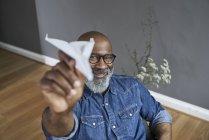 Älterer Mann hantiert mit Papierflieger — Stockfoto