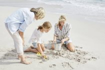 Family playing with sand — Stock Photo