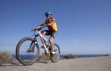 Senior man riding mountain bike — Stock Photo