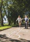 Senior woman playing hopscotch while husband — Stock Photo