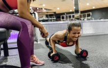 Woman with trainer working out — Stock Photo