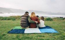 Сім'я з собакою, сидячи на ковдру — стокове фото