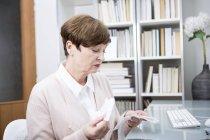 Senior femme, vérification des factures — Photo de stock